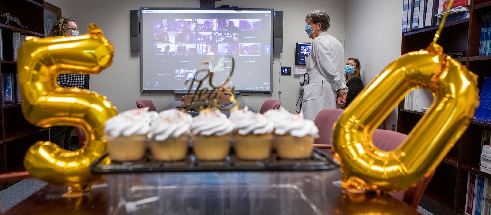 A photo shows balloons with the numbers 5 and 0 and a lot of cupcakes. A woman is standing in the background, smiling.