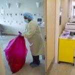 Woman standing in yellow gown, blue hair cover, blue facemask, blue gloves and blue shoe covers holds a red bag while removing red-bag waste from a patient room.