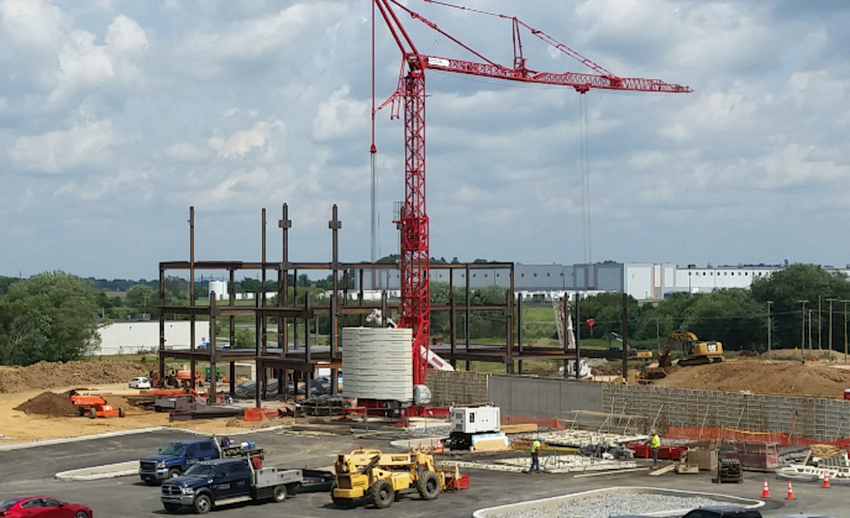 A hospital construction site shows a crane and steel beams