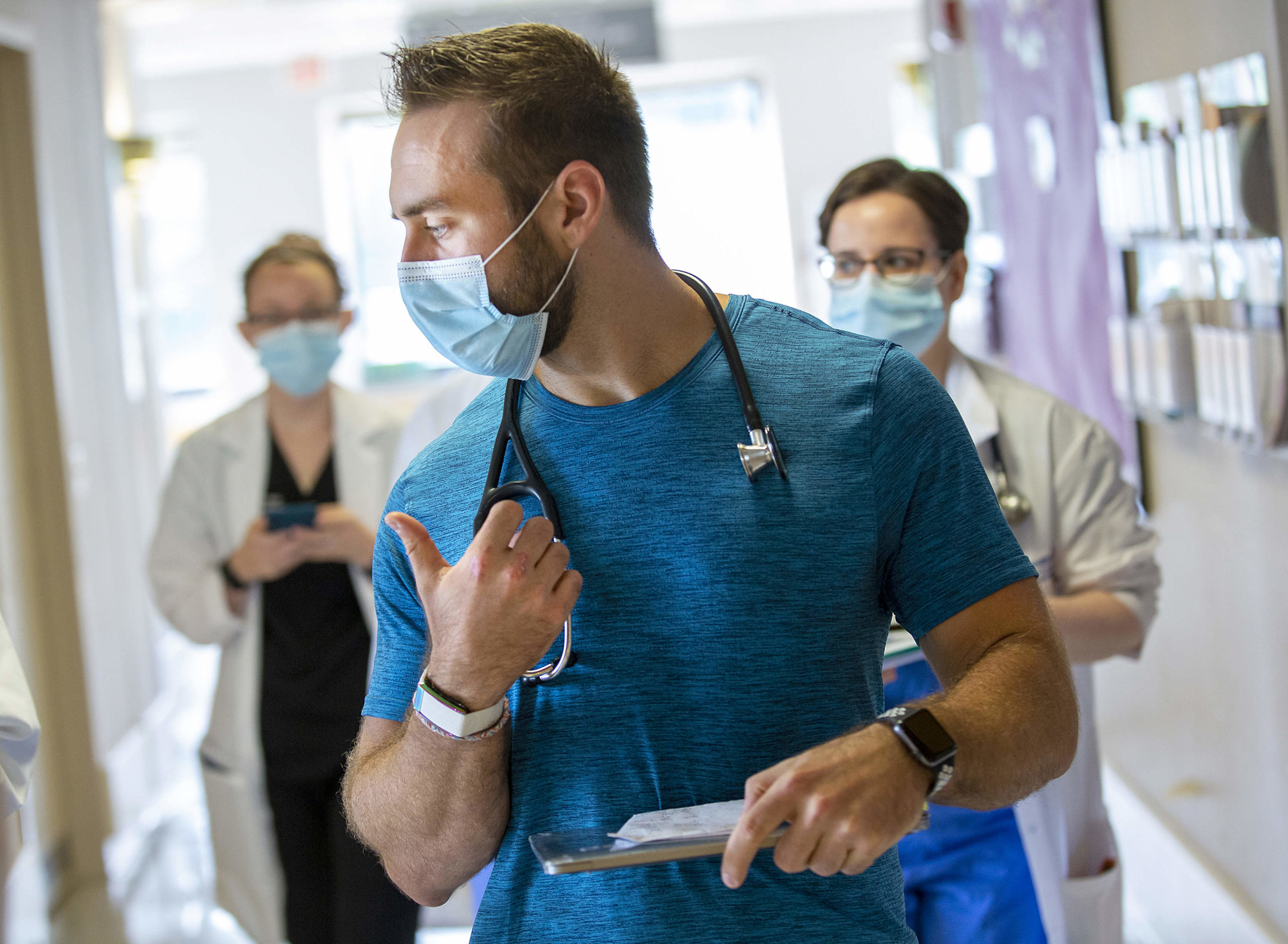 Dr. Alexander Hajduczok, a third-year internal medicine resident at Penn State Health Milton S. Hershey Medical Center, sports a wearable device manufactured by WHOOP on his right wrist. Two other physicians are behind him, walking down a hallway.