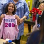 Ruth Vega smiles as she holds a sweatshirt up in front of herself that says Penn State 2000th. Her parents stand behind her. A poinsettia plant sits on a table in the background, with people sitting around it.