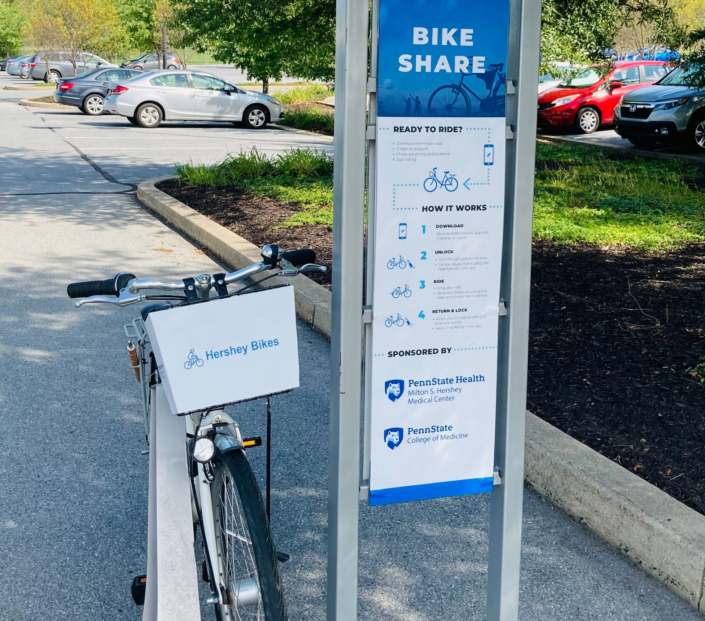 A bicycle is seen on a rack next to a sign describing the bike share program.