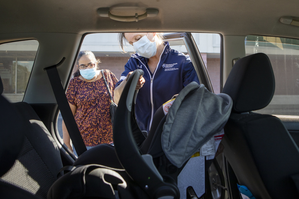Two women stand outside of a car, looking in at an infant seat in the back seat.