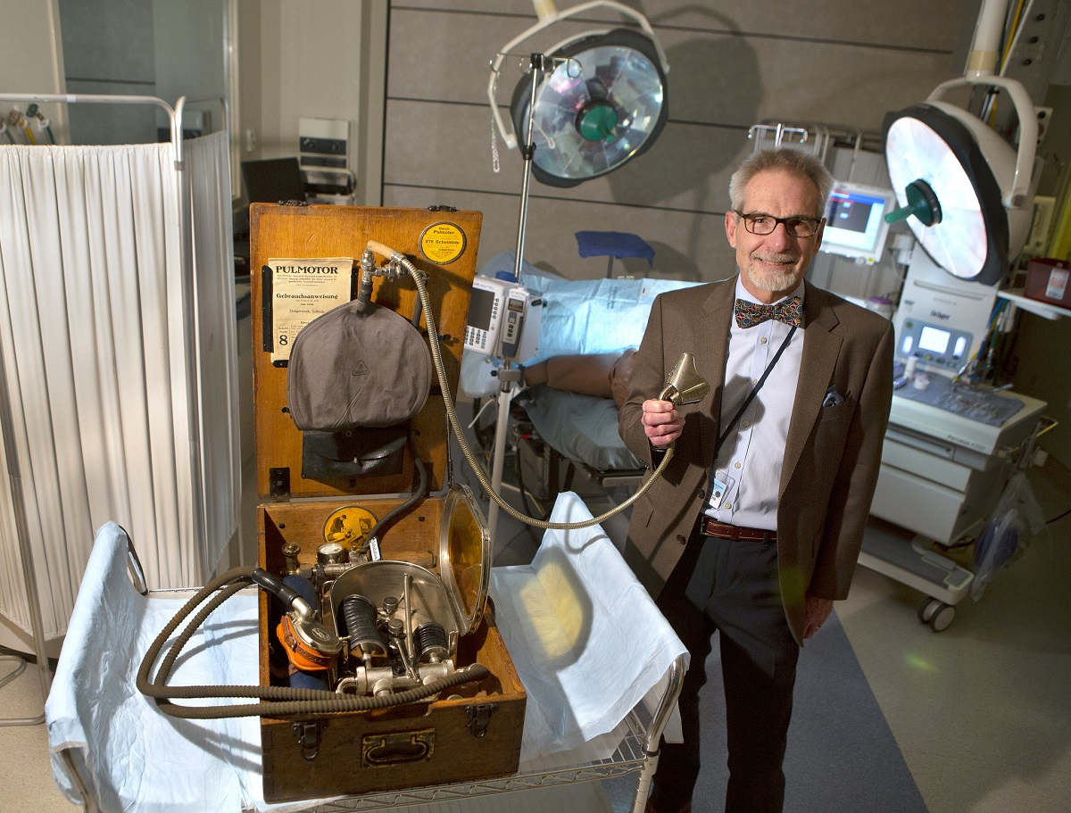Dr. Berend Mets stands next to an old machine in a wooden case. He holds a mouthpiece at the end of a hose attached to it. He stands in a hospital room, surrounded by medical equipment.