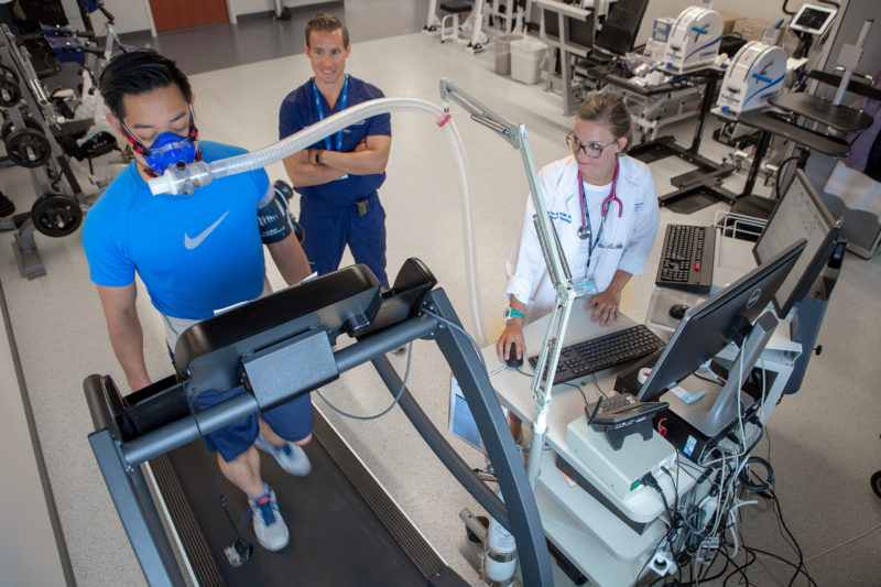 A patient walks on a treadmill wearing a face mask in the lab of Dr. Jonathan Stine at Penn State Health Milton S. Hershey Medical Center. Dr. Stine and exercise physiologist Brei Hummer are watching the patient.