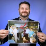 Kristofer Miller, who has a beard and moustache and is smiling, holds up a picture of a group of people. A red arrow drawn on the picture shows him among six co-workers, who are standing by stacks of large cardboard boxes and laundry bins.
