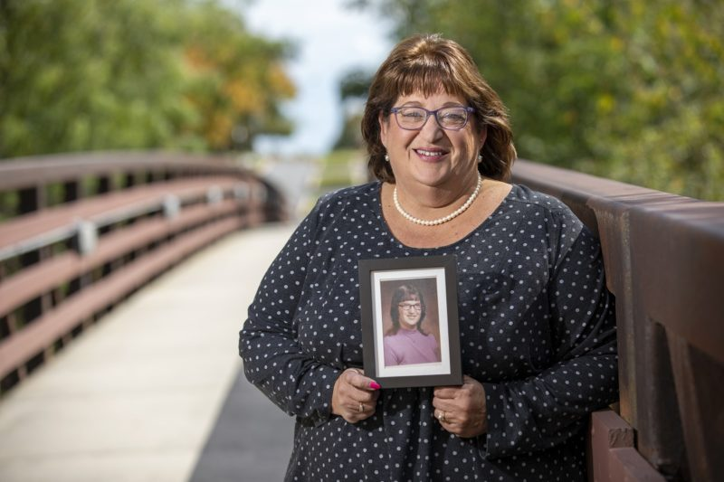 Carolyn Powell, who wears glasses and is smiling, smiles and holds a picture of herself taken in her early days at Hershey Medical Center. She is wearing a polka-dotted blouse and a string of pearls and stands on a bridge with trees in the background.