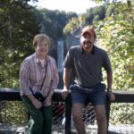Glenna and J. David Brensinger lean against the side of a bridge. In the background are trees and, at a distance, a large waterfall.