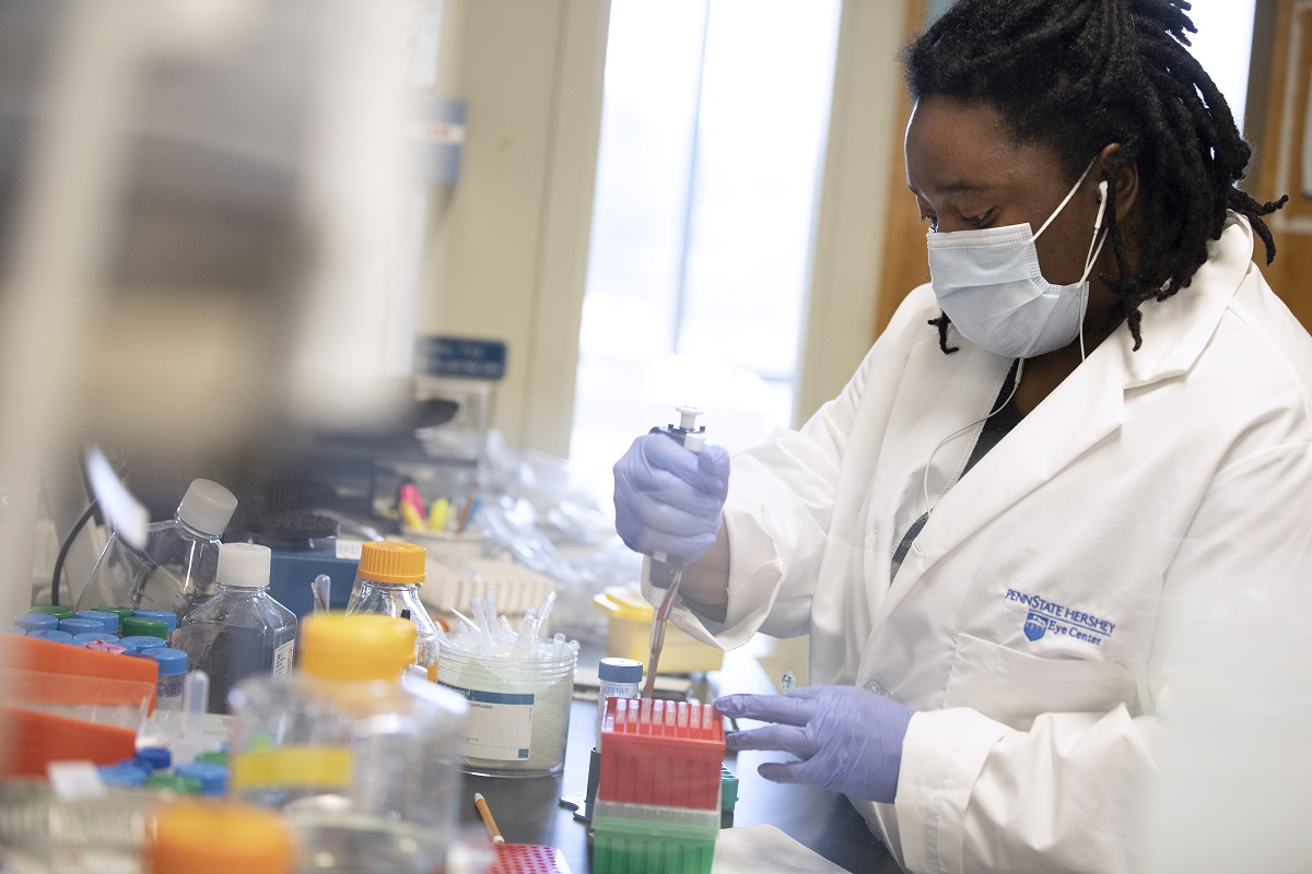 Jasmine Geathers is working in a lab at Penn State College of Medicine. She is wearing a white coat with the Penn State Hershey logo on it, a face mask and gloves. She is holding an instrument in a container of test tubes. A table full of bottles and other lab equipment is in front of her.
