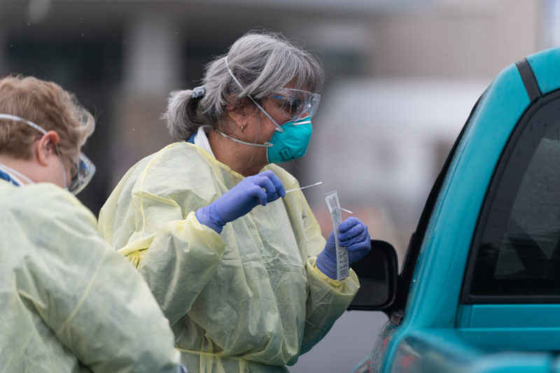 Two women in personal protective equipment, including gowns, masks, goggles, and gloves, stand alongside a vehicle, speaking to the driver, who's not visible. One worker holds a swab.