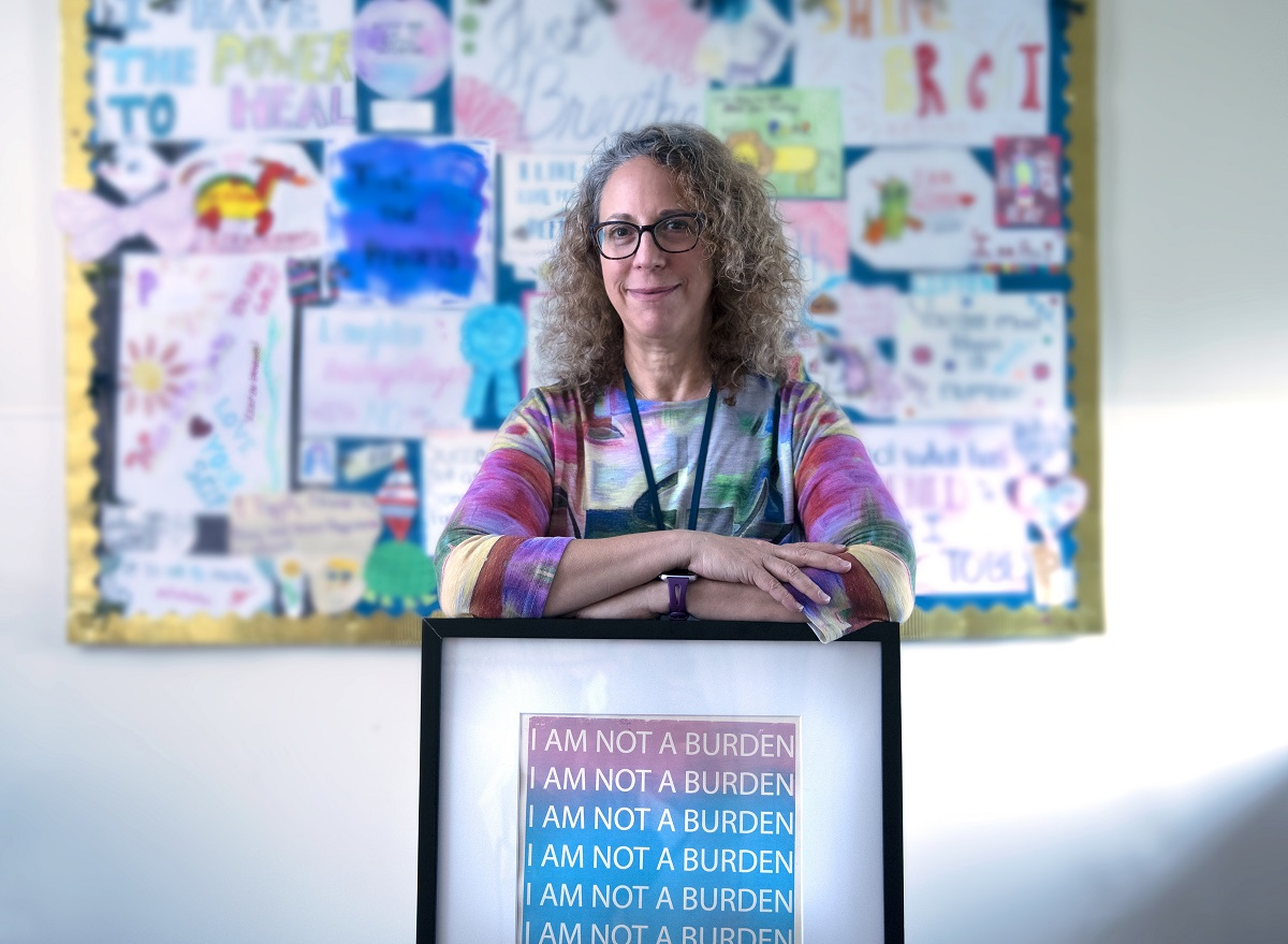 "Amy Keisling, Gender Health Clinic coordinator, smiles as she leans on a framed picture that says ""I am not a burden."" She has curly hair and is wearing glasses and a lanyard. Behind her is a bulletin board out of focus."