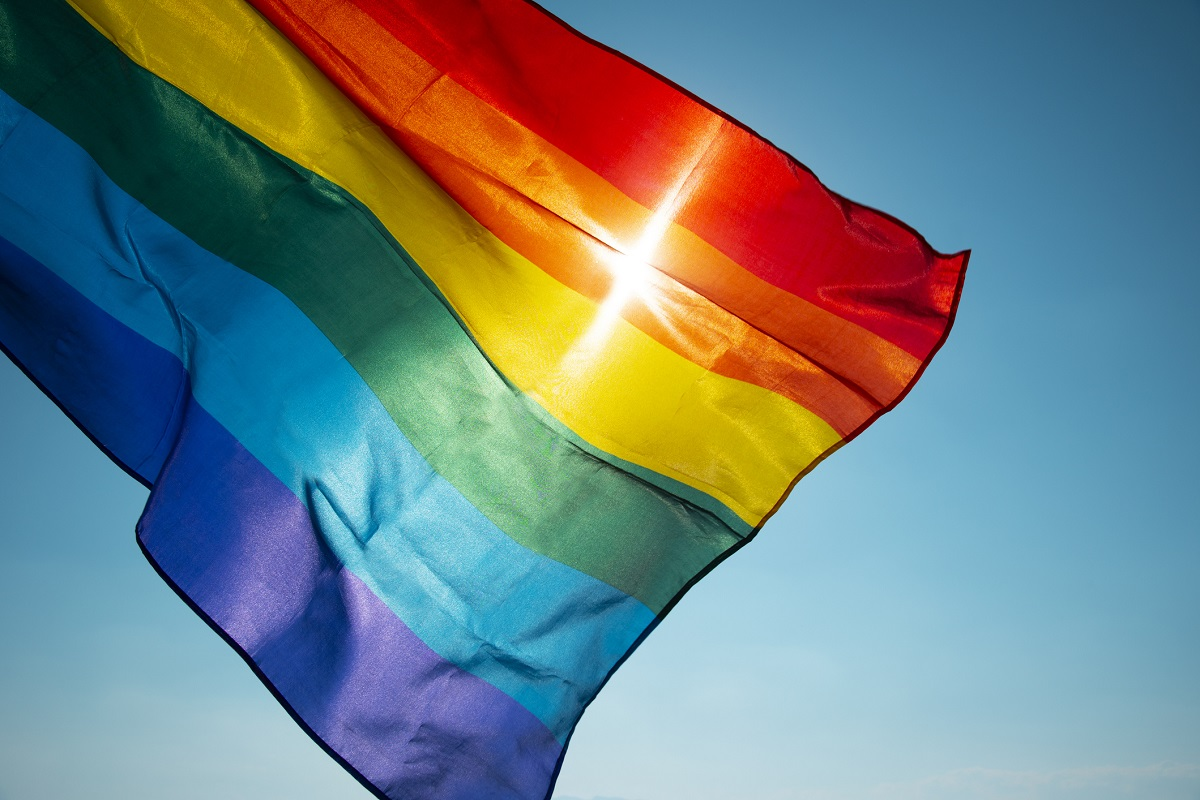 A flag with rainbow stripes waves in front of the sun.