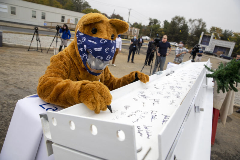 """The """"Nittany Lion,"""" wearing a facemask, uses a marker to sign a metal beam. Several people walk around in the background."""