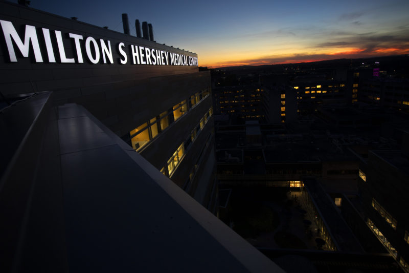 """An illuminated sign reading """"Milton S. Hershey Medical Center"""" appears on a building at dusk."""