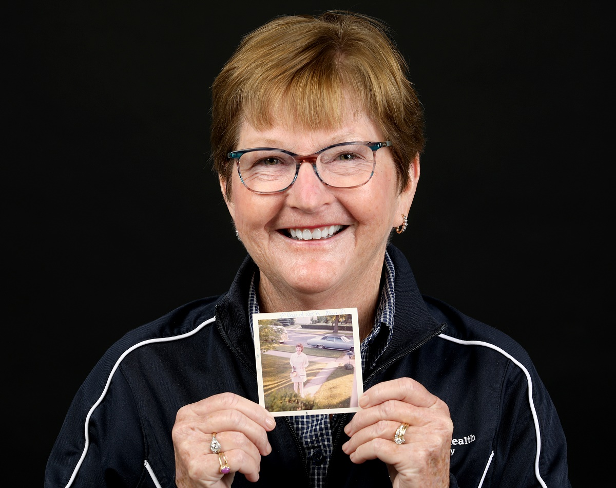 Janice Mills, who has short hair and glasses, smiles and holds a vintage picture of herself in a nurse's uniform.
