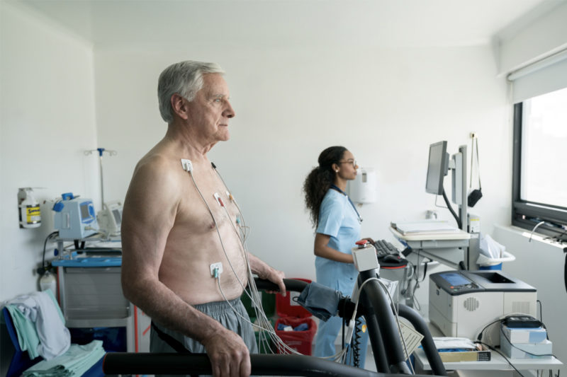 A man wears several electrodes on his chest as he walks on a treadmill. A woman in scrubs is in the background, working on a computer.