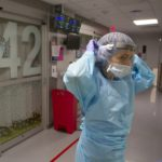 Dr. Jennifer Cooper puts on a face shield, mask, gown and rubber gloves. Behind her, decals pepper a sliding glass door.