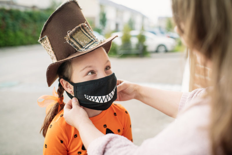 Young girl dressed for Halloween in brown top hat and pumpkin shirt gets her black smiley-face cloth facemask fitted by her mother prior to trick-or-treating.