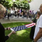 Two women fold the American flag. A crowd of people watch from a distance.