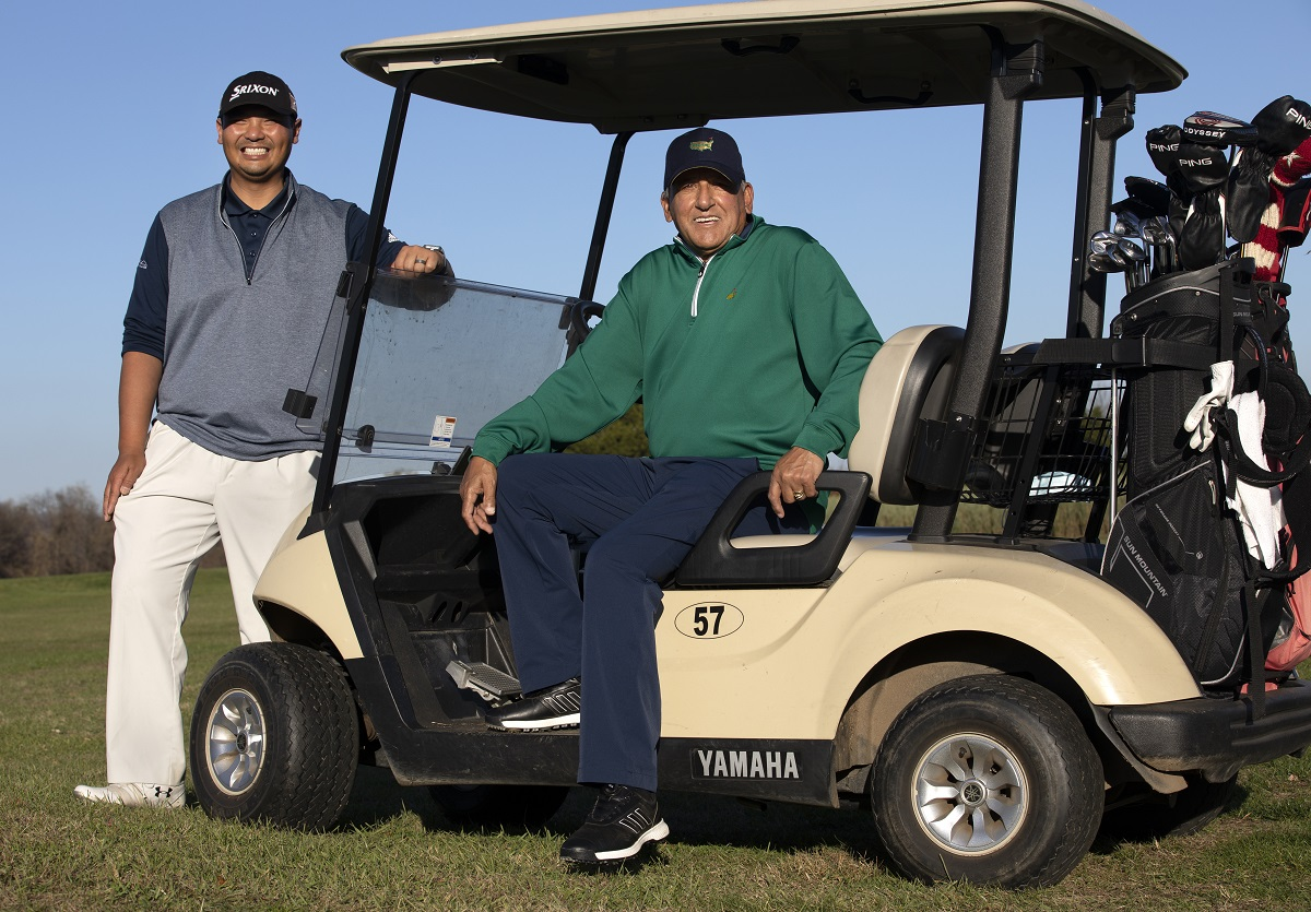 One man sits in and another stands next to a golf cart in a grassy area on a sunny day.