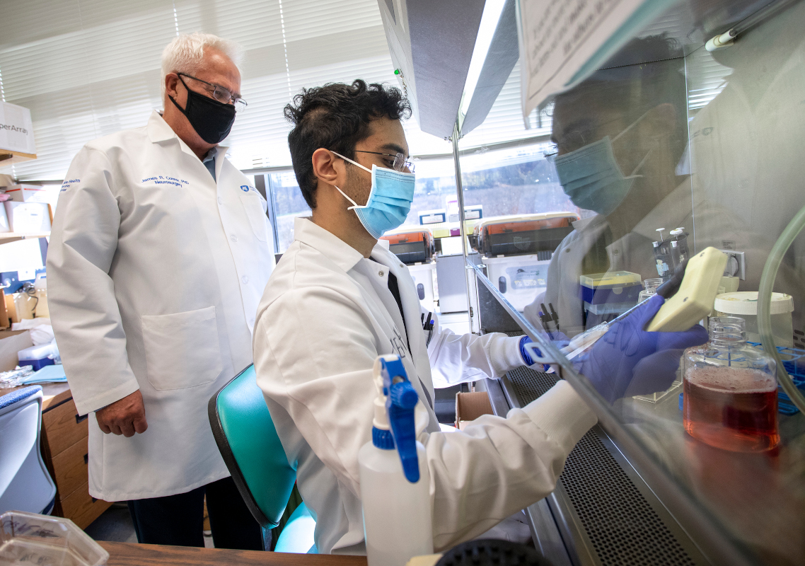 Two men in doctors' coats work in a research lab
