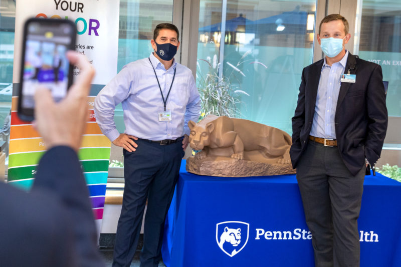 Two men wearing masks pose for a photo next to a statue of a lion