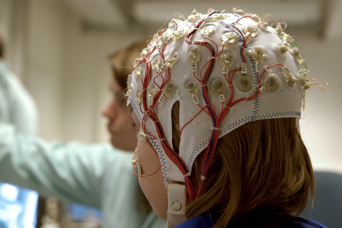 A female wears a rubber treatment cap lined with electrodes as a medical professional stands nearby.