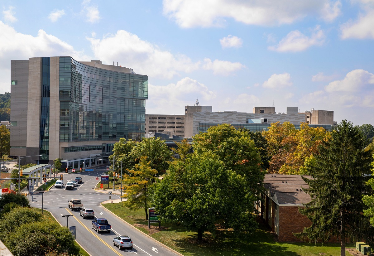 Image shows the outside of Hershey Medical Center with trees in fall colors.