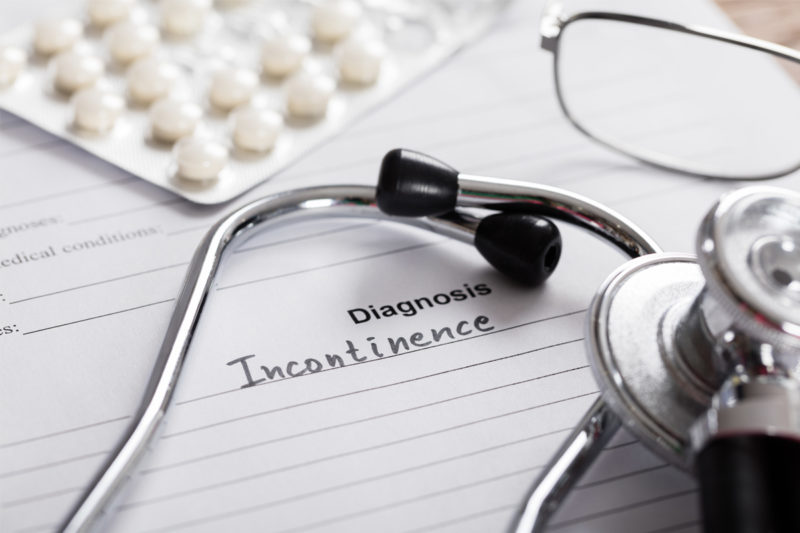 "A piece of paper with the words ""Diagnosis Incontinence"" sits on a desk. On top of it are a stethoscope, pack of pills and reading glasses."