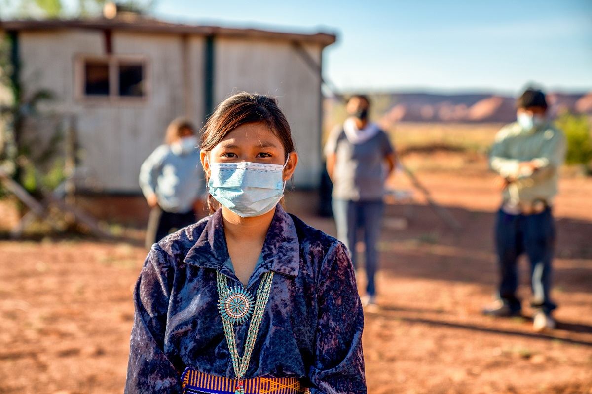 Native American teen-aged girl wears a face mask and a beaded necklace. Standing behind her are three other people wearing face masks near a building.