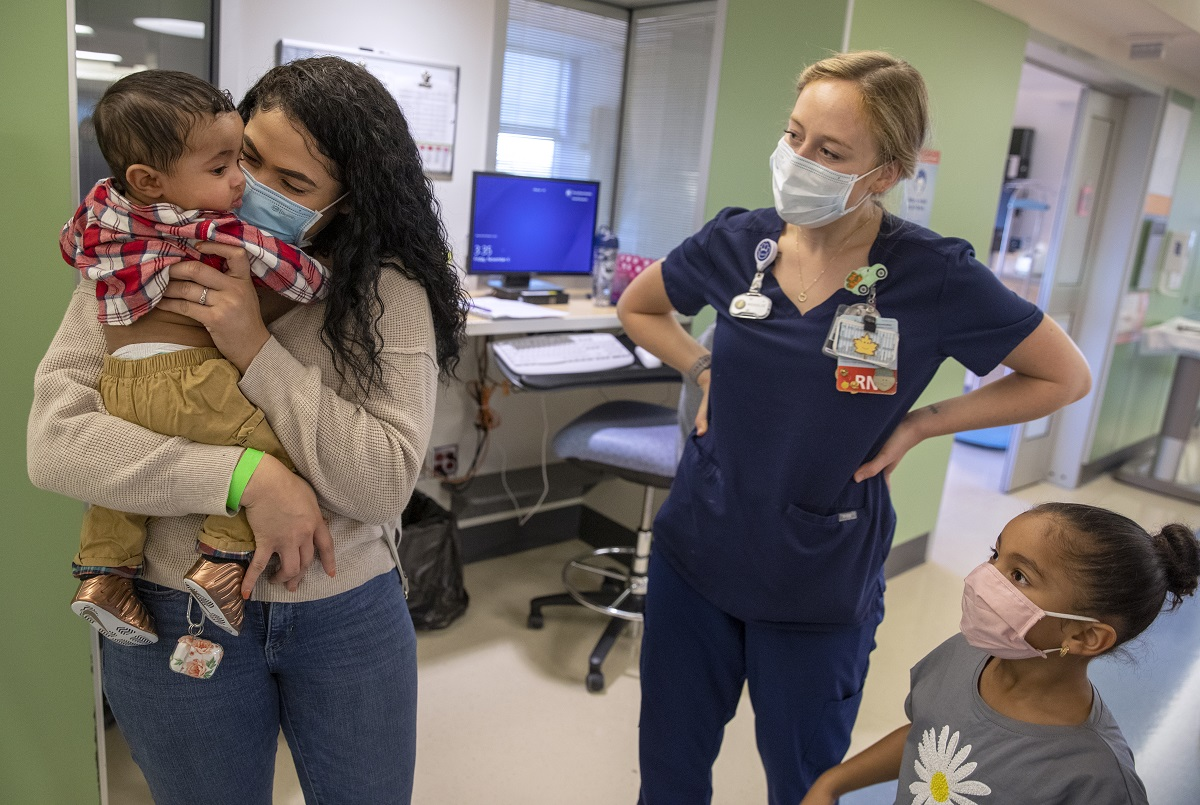 Terianny Vicente holds son Calvin, who is wearing a plaid shirt and pants, as Jo Rosenberger and Calvin's big sister look on. Vicente, who has long hair, wears a sweater, jeans and a mask. Rosenberger wears scrubs and a mask. Hospital equipment and computer monitors are in the hallway behind them.
