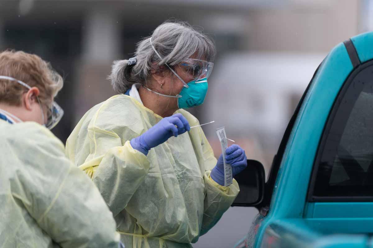 Dos mujeres con equipo de protección personal, incluyendo batas, máscaras, gafas y guantes, se paran junto a un vehículo, hablando con el conductor, que no es visible. Un trabajador tiene un hisopo.