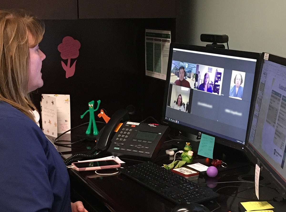 Director of women's and children's services Kirsten Hakim looks at her computer monitor, as she participates in an online career readiness session. There is a black keyboard, black phone and pink mobile phone on the desk in front of her.