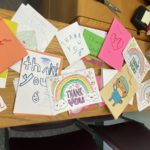 "More than a dozen handmade cards cover a wooden desk. Some have pictures of rainbows, doctors and hearts and words that say ""kind,"" ""giving,"" ""thoughtful"" and ""hero."""