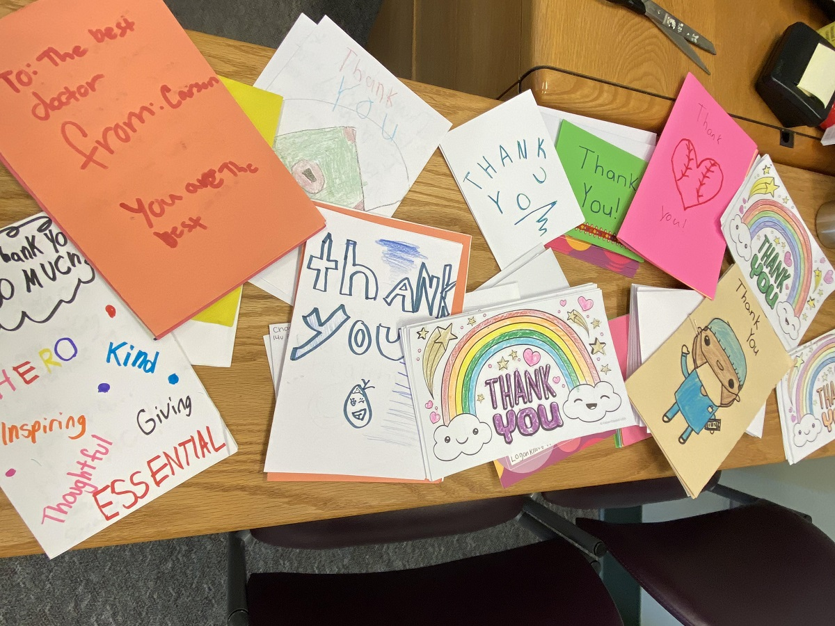 """More than a dozen handmade cards cover a wooden desk. Some have pictures of rainbows, doctors and hearts and words that say """"kind,"""" """"giving,"""" """"thoughtful"""" and """"hero."""""""