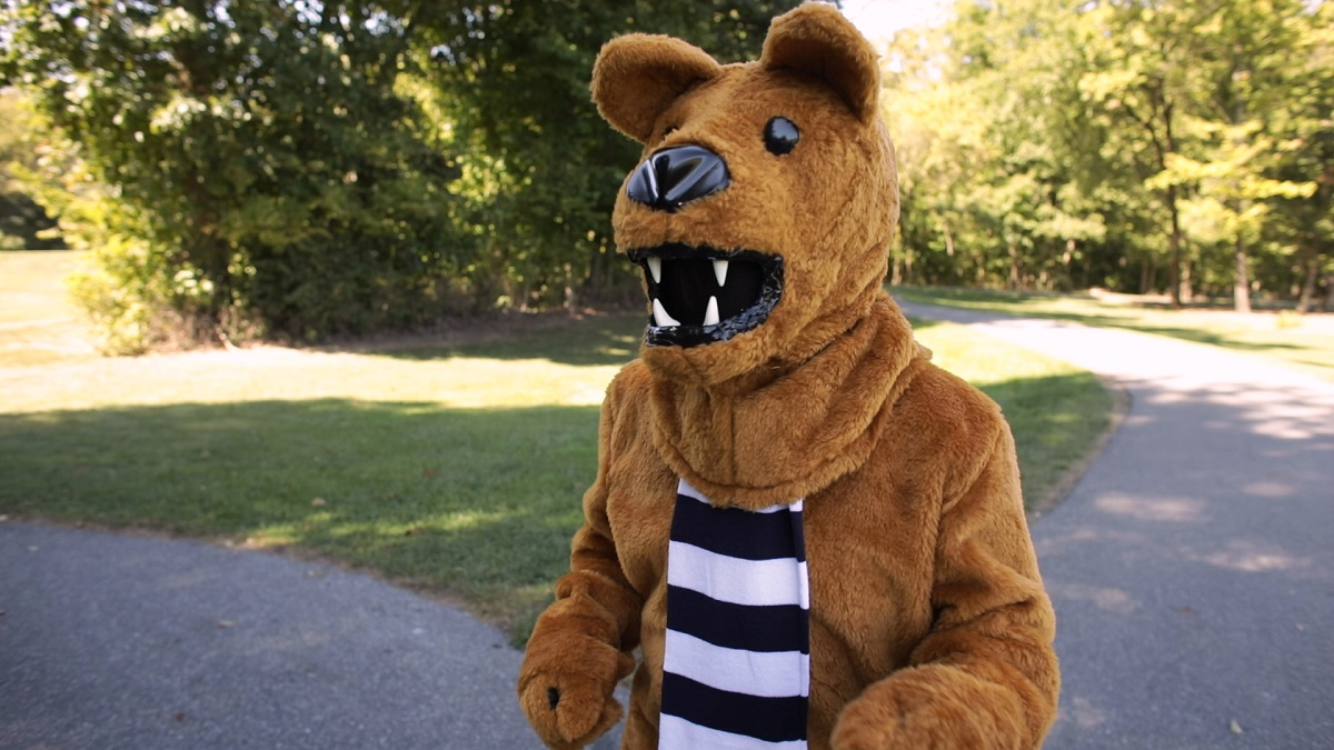 Person dressed as the Penn State Nittany Lion and wearing a scarf runs along a path. Behind him are two asphalt paths, grass and trees.