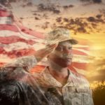 A Black woman in a U.S. Army soldier uniform salutes. An American flag is in the background against a sunset and trees.
