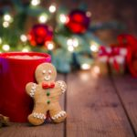 A gingerbread man leans against a mug containing a hot liquid. Behind them holiday decorations are seen out of focus.