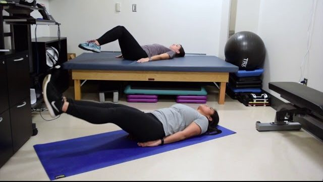 A still from a video shows two people performing the Leg Raises exercise.