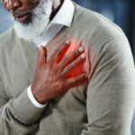 A man wearing a sweater places his right hand over his heart, apparently in chest pain.