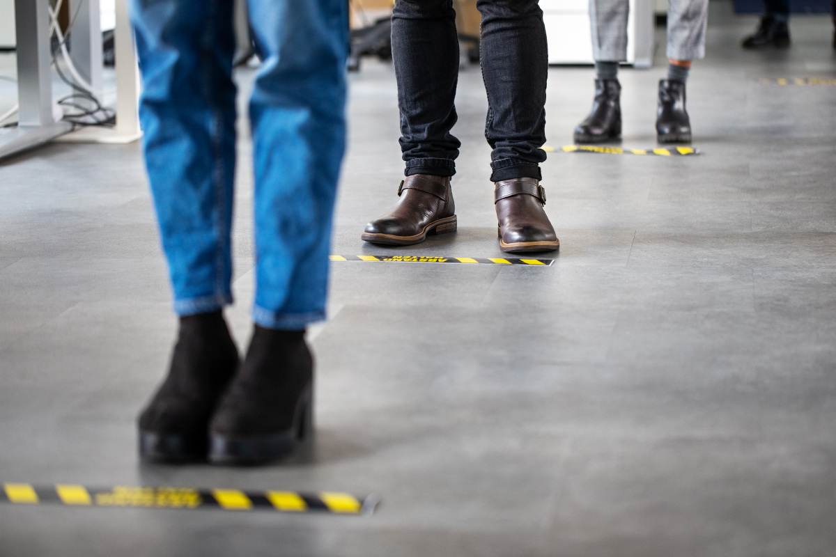 Pictured from the knees down, people stand at a series of taped-off lines on a floor.