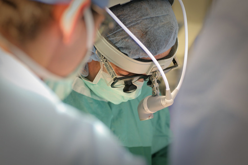 A surgeon and other staff lean over an operating table.