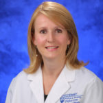 Head and shoulders photo of Dr. Sarah Iriana. She has shoulder length strawberry blonde hair and is wearing a white coat.