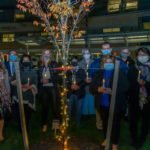 A group of 12 people stand behind a small tree decorated in lights at night. They are holding lit, battery-operated candles. Behind them is Penn State Children's Hospital.