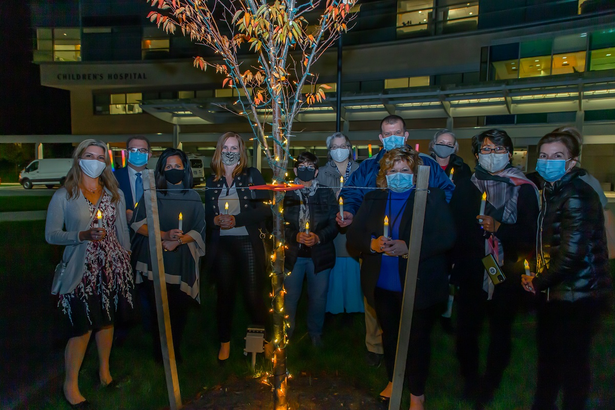 A group of 12 people stand behind a small tree decorated in lights at night. They are holding lit, battery-operated candles. Behind them is Penn State Health Children's Hospital.