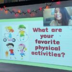 """A computer screen shows Estelle Greene in a window in the upper left corner. The screen features the words """"What are your favorite physical activities?"""" with animated characters"""