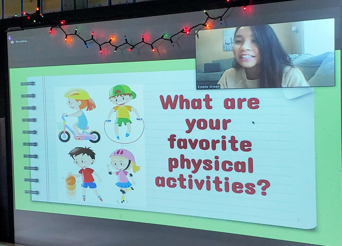 "A computer screen shows Estelle Greene in a window in the upper left corner. The screen features the words ""What are your favorite physical activities?"" with animated characters"