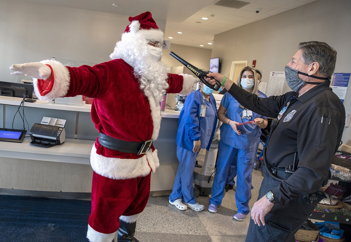 A man in a Santa Claus suit is wanded by a security guard while people in scrubs and surgical masks look on.