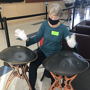 A woman wearing a mask and gloves sits behind two percussion instruments.