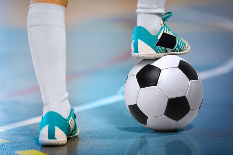 Close-up of an athlete's legs as they stand on a gym floor, the right foot resting on a soccer ball.